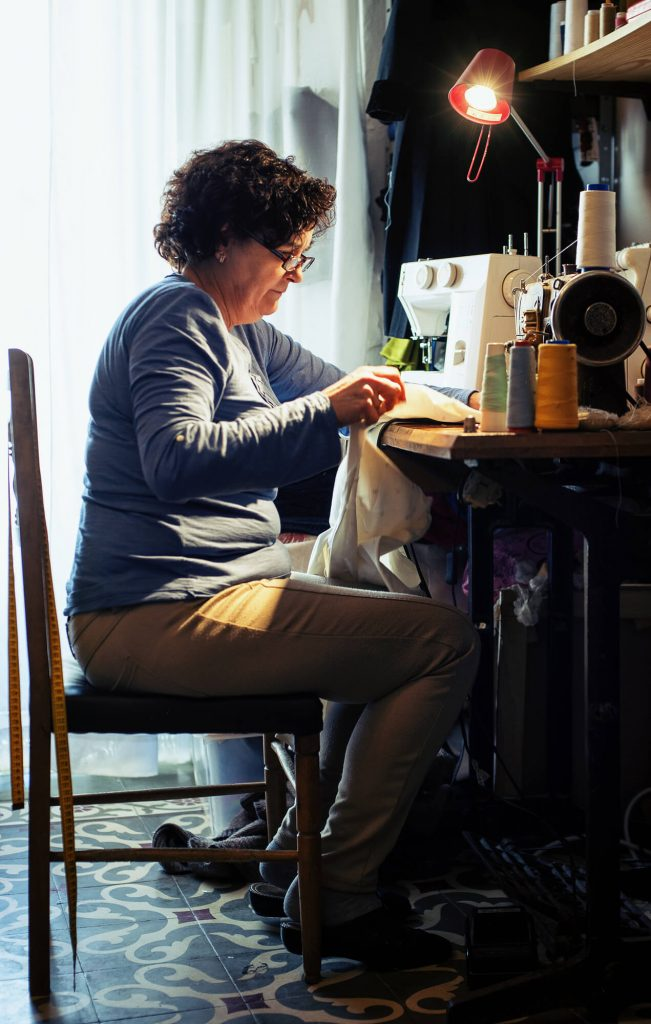 A Middle Aged Woman is Sewing